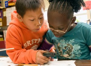 Young students looking through magnifying glass